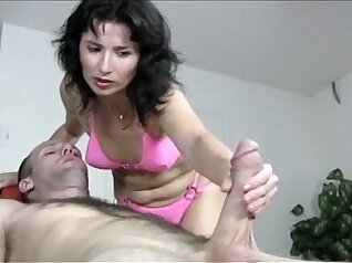Another MILF massaging her slave and giving him handjob
