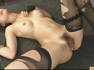 skinny woman is in her bed, caressing her pussy with a large toy